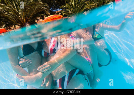 Italy, Sardinia, Alghero, Mother with children (14-15, 16-17) hugging at swimming pool - Stock Photo