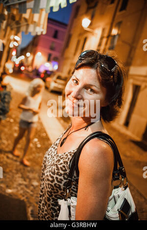 Italy, Sardinia, Alghero, Mother with daughter (14-15) in street at night - Stock Photo