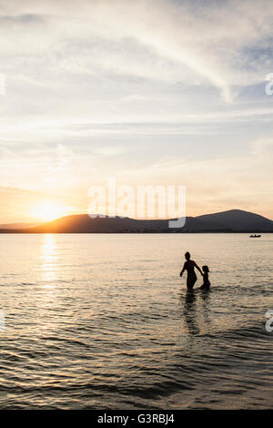 Italy, Sardinia, Alghero, Mother and daughter wading in sea at sunset - Stock Photo