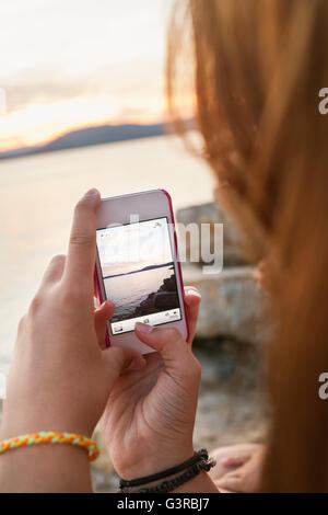 Italy, Sardinia, Alghero, Teenage girl (16-17) taking picture of sea at sunset with smart phone - Stock Photo