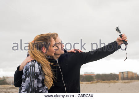Sweden, Skane, Malmo, Young couple taking selfie on beach - Stock Photo