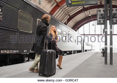 Sweden, Skane, Malmo, Young couple talking at railroad station - Stock Photo