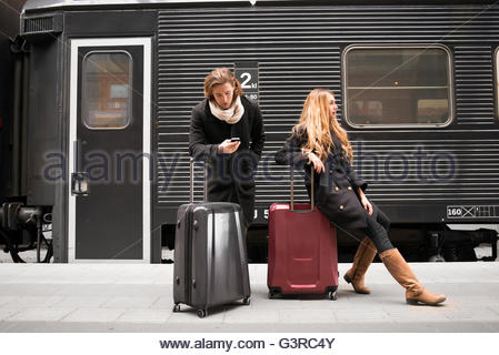 Sweden, Skane, Malmo, Young couple waiting for train - Stock Photo