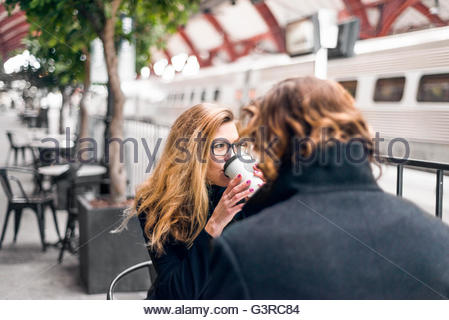 Sweden, Skane, Malmo, Mid-adult woman drinking coffee at sidewalk cafe - Stock Photo
