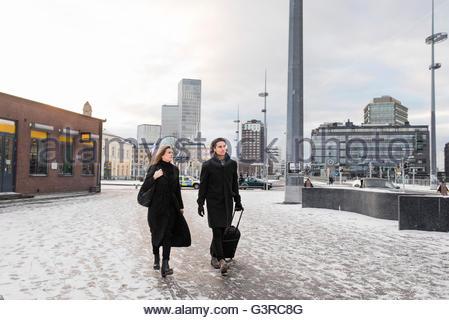 Sweden, Skane, Malmo, Couple with wheeled luggage walking through city - Stock Photo