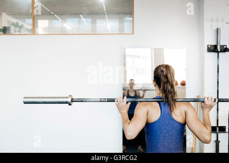 Germany, Young woman training with barbell in gym - Stock Photo