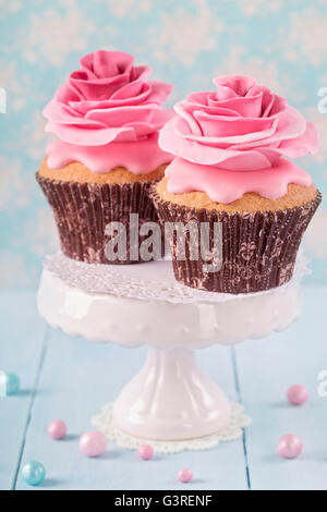 Two cupcakes with rose flowers - Stock Photo