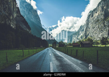 A road stretching in a gigantic valley in Lauterbrunnen, Switzerland - Stock Photo