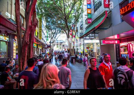 A street scene in the Chinese quarter of Sydney, Australia with many shoppers buying and eating. - Stock Photo