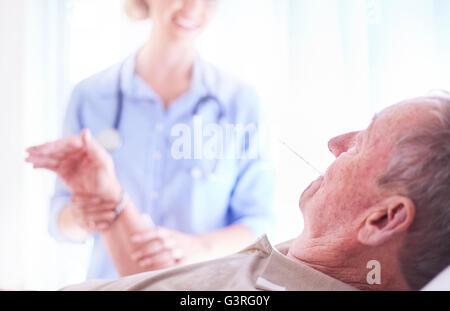 Doctor checking senior man's pulse and temperature at checkup - Stock Photo