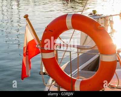 Closeup rescue red lifebuoy life preserver saver ring on sailboat and polish ensign flag - Stock Photo