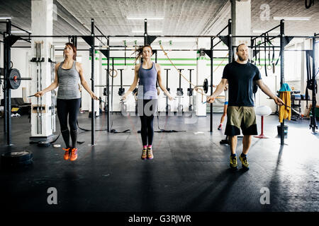 Germany, Young women and man skipping rope in gym - Stock Photo