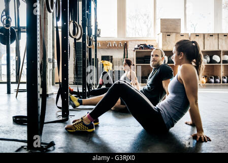 Germany, Young women and men sitting on floor in gym - Stock Photo