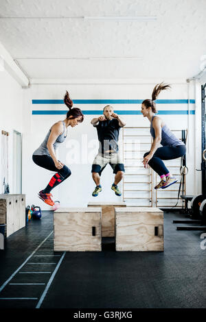 Germany, Young women and man jumping in gym - Stock Photo