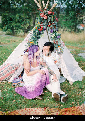 Sweden, Bride and groom sitting on grass in front of white tent at hippie wedding - Stock Photo