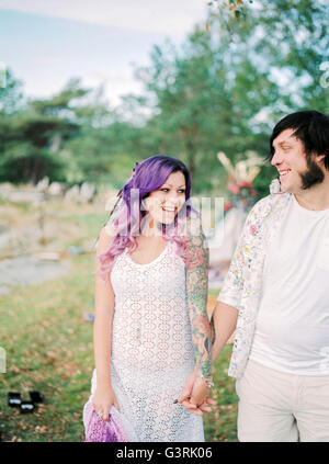 Sweden, Bride and groom standing holding hands at hippie wedding - Stock Photo