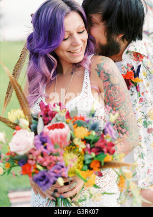 Sweden, Groom kissing bride at hippie wedding - Stock Photo