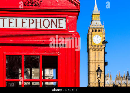 Iconic red telephone box with Big Ben against blue sky in the background - Stock Photo