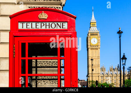 Iconic red telephone box with Big Ben and street lamps against blue sky in the background - Stock Photo