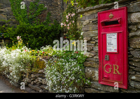 An old-fashioned post box in a traditional English countryside village. - Stock Photo