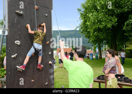 Massagno, Switzerland - 12 June 2016 - Effort of a boy in climbing a wall to reach the top - Stock Photo
