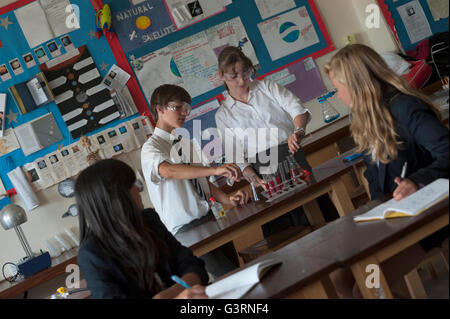 Secondary school pupils taking part in a chemistry experiment in science class. England. UK - Stock Photo