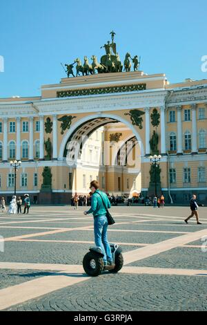 Saint Petersburg Russia. Tourist riding Segway across Palace Square in front of double arch of the General Staff - Stock Photo