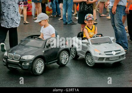Saint Petersburg, Russia. Boys test drive German import cars on Ostrovsky Square during annual St. Petersburg City - Stock Photo