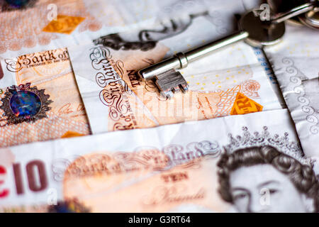 House keys and British pound bank notes depicting cost of moving, rent or mortgages