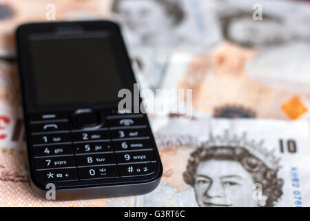 Mobile phone and ten pound note depicting cost of phones - Stock Photo