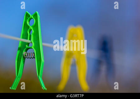 Colored clothes pegs on washing line - Stock Photo