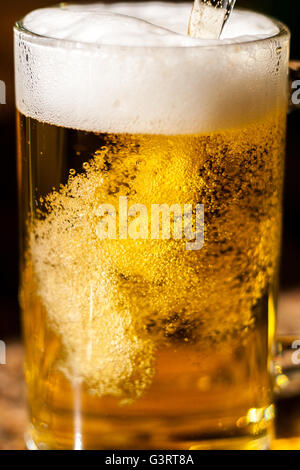 Beer or larger being poured into a glass - Stock Photo