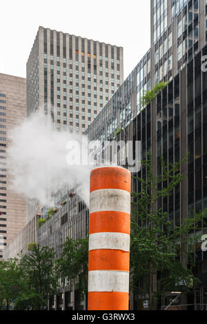 Steam rising out of a subway vent in a street of New York City - Stock Photo