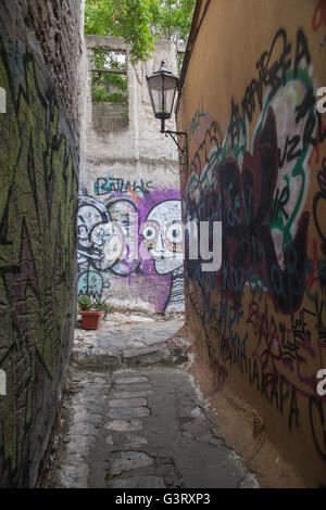One of the tiny alleys in the historic neighborhood of Anafiotika, central Athens, covered in street art and graffiti. - Stock Photo
