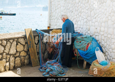 An old fisherman repairing his nets at Sorrento, near Naples, Italy - Stock Photo