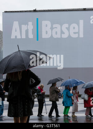 Basel, Switzerland. 14 June, 2016. Visitors are queuing up in the pouring rain outside Basel's exhibition centre - Stock Photo