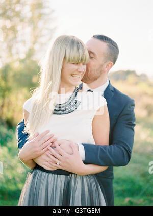 Sweden, Groom embracing bride - Stock Photo