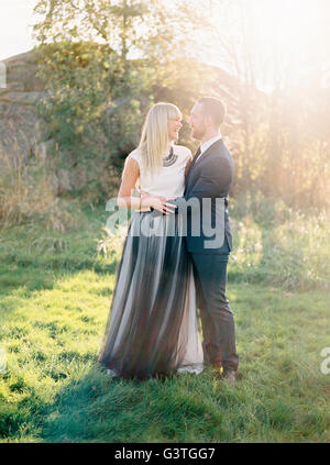 Sweden, Groom and bride standing together in grass - Stock Photo