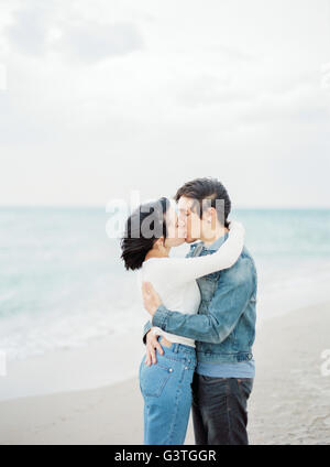 Spain, Valencia, Couple embracing and kissing on beach - Stock Photo