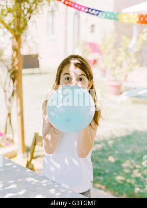 Italy, Boy (8-9) inflating blue balloon - Stock Photo