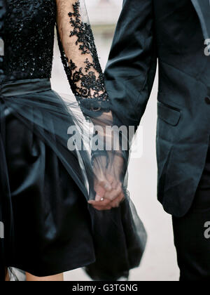 Sweden, Young formally dressed couple holding hands - Stock Photo