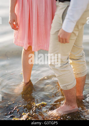 Sweden, Bohuslan, Fjallbacka, Couple standing barefoot in water - Stock Photo