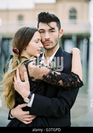 Sweden, Halland, Varberg, Young formally dressed couple hugging - Stock Photo