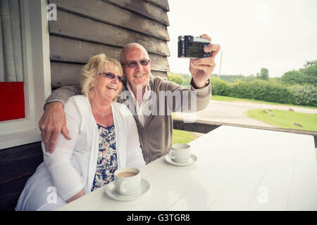 UK, England, Lincolnshire, Louth, Senior couple sitting at table on porch and taking selfie with camera - Stock Photo