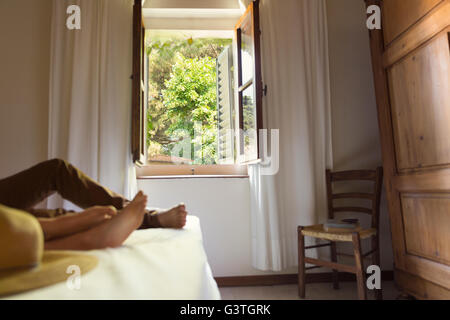 Italy, Couple lying on bed in farmhouse - Stock Photo