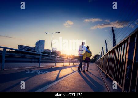 Sweden, Stockholm, Couple walking on bridge - Stock Photo