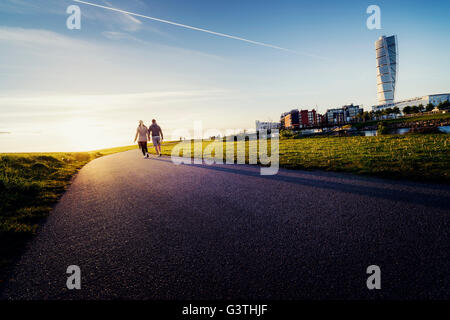 Sweden, Skane, Malmo, Ribersborg, Mid-adult couple holding hands - Stock Photo