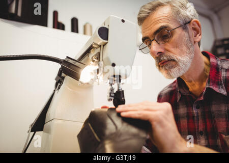 Low angle view of cobbler using the sewing machine - Stock Photo