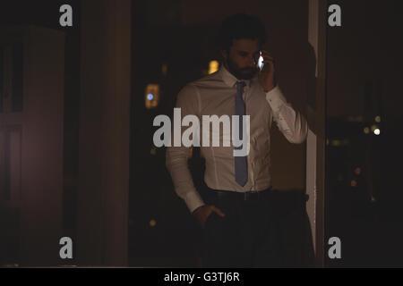 Businessman making a phone call at night - Stock Photo