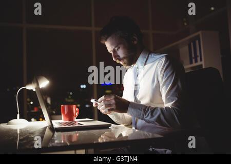 Businessman using smartphone at night - Stock Photo